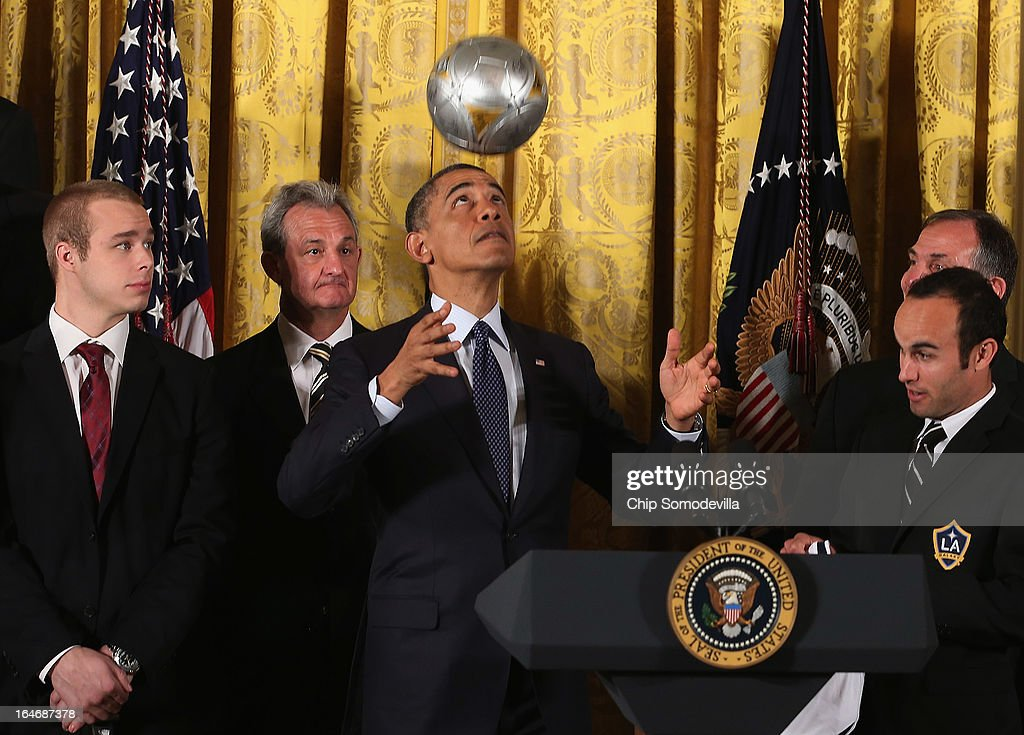 U.S. President Barack Obama (C) bounces a soccer ball on his head while hosting a ceremony honoring players and coaches from the National Hockey League Stanley Cup-winning Los Angeles Kings and the Major League Soccer champions Los Angeles Galaxy in the East Room of the White House March 26, 2013 in Washington, DC. After the White House honors both California teams, players will participate in a question-and-answer panel with Sam Kass, Assistant White House Chef and Executive Director of first lady Michelle Obama's health program 'Let's Move!'