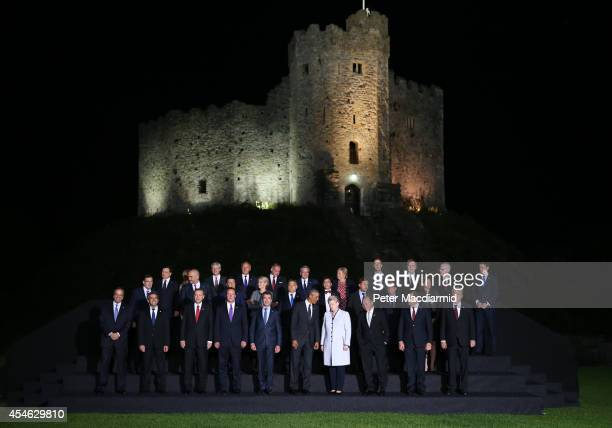 President Barack Obama British Prime Minister David Cameron and NATO Secretary General Anders Fogh Rasmussen talk as they pose with other leaders and...