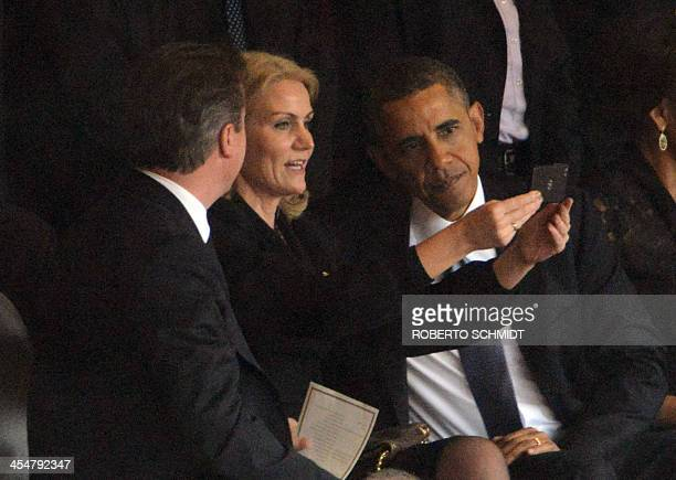 US President Barack Obama British Prime Minister David Cameron look at a selfie picture taken by Denmark's Prime Minister Helle Thorning Schmidt...