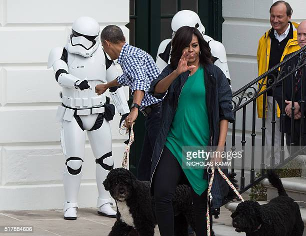 US President Barack Obama bumps fists with a Star Wars Stormtrooper as First Lady Michelle Obama waves to the crowd at the annual Easter Egg Roll at...