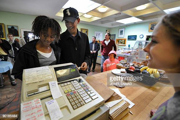 US President Barack Obama buys a pack of gum for his daughter Malia at a coffee shop on Martha's Vineyard Massachusetts on August 30 2009 AFP...