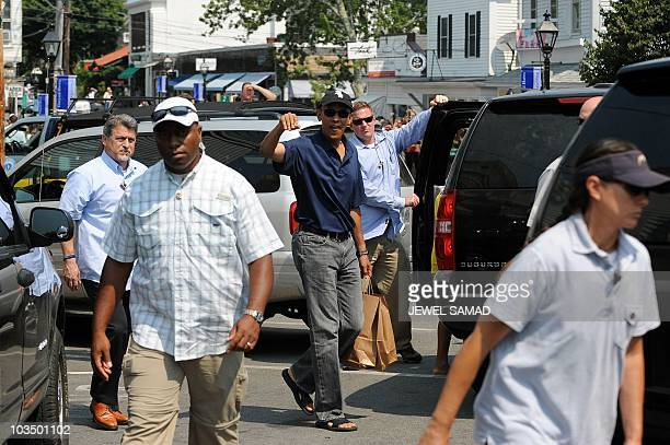 US President Barack Obama carries bags after shopping at Bunch of Grapes bookstore with his daughters Malia and Sasha in Vineyard Haven on Martha's...
