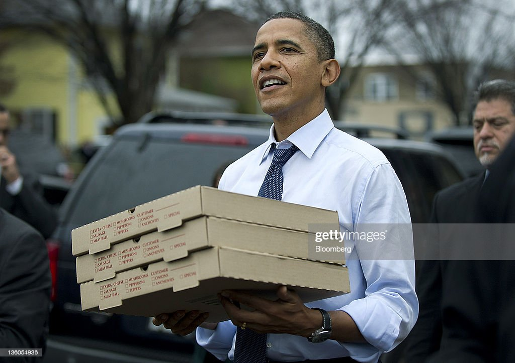 U.S. President Barack Obama carries boxes of pizza from Del Ray Pizzeria in Alexandria, Virginia, U.S., on Wednesday, Dec. 21, 2011. Paychecks for 160 million workers will be reduced in January unless lawmakers break a stalemate that could dent U.S. economic growth and poses political difficulties for a Congress with low public approval ratings. Photographer: Kevin Dietsch/Pool via Bloomberg via Getty Images