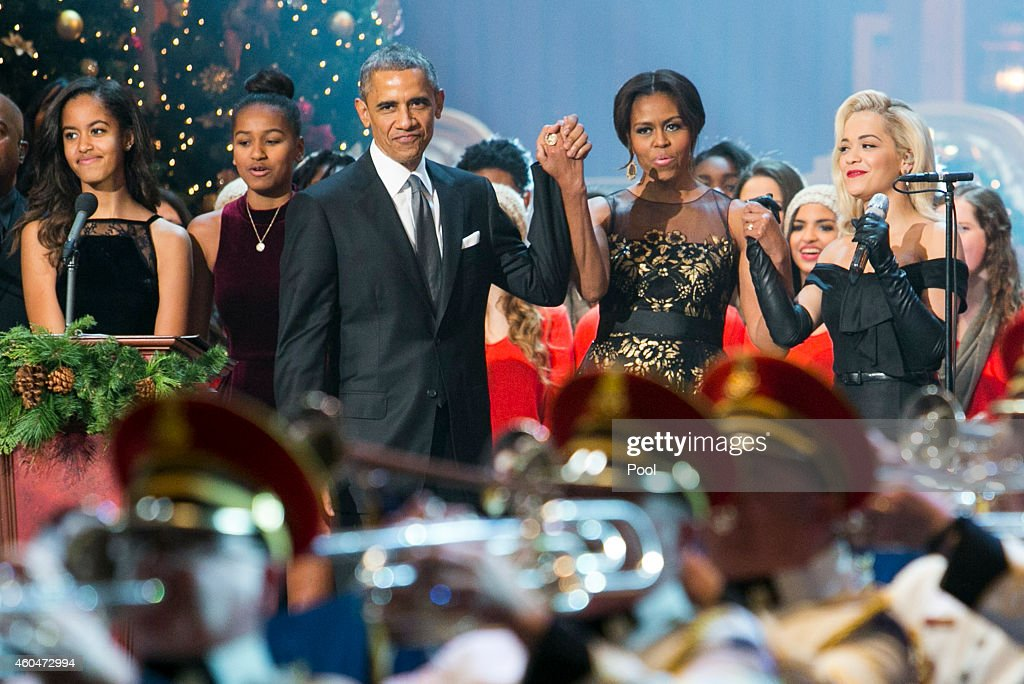 U.S. President Barack Obama, center left, first lady Michelle Obama, center right, daughters Malia and Sasha, left, and singer Rita Ora, right, join the performers on stage during the taping of TNT's 'Christmas in Washington' program on December 14, 2014 in Washington, DC. Proceeds from the concert will go to Children's National Medical Center.