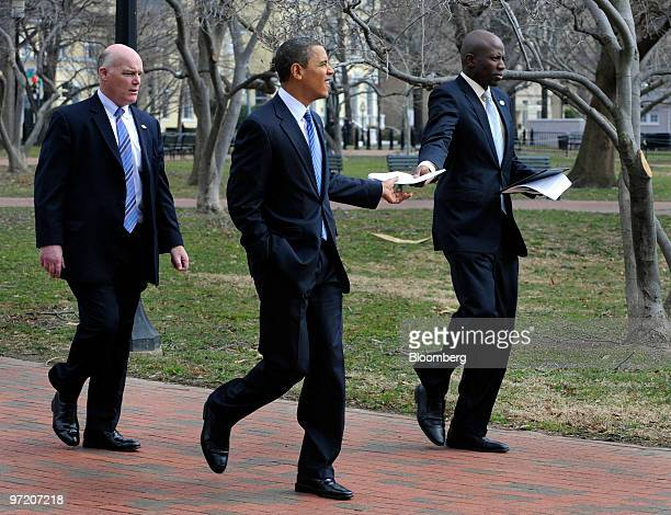 US President Barack Obama center receives a paper from aide Reggie Love right as they walk through Lafayette Park on their way back to the White...