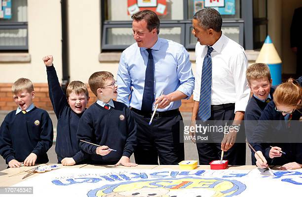 S President Barack Obama center right and British Prime Minister David Cameron center left help students as they work on a school project about the...