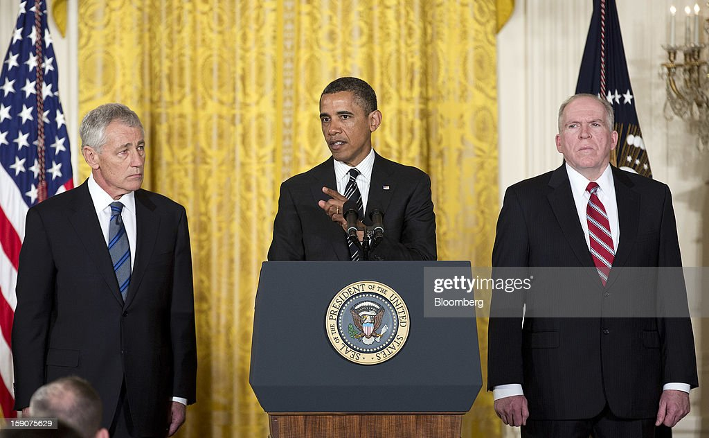 "U.S. President Barack Obama, center, stands with his nominee for Secretary of Defense Chuck Hagel, left, a former Republican Senator from Nebraska, and his nominee for director of the Central Intelligence Agency, John Brennan, White House chief counterterrorism adviser, during an announcement in the East Room of the White House in Washington, D.C., U.S., on Monday, Jan. 7, 2013. ""Chuck Hagel is the leader that our troops deserve,"" Obama said today in an announcement combining his choices of Hagel for the Pentagon and Brennan to head the Central Intelligence Agency. Photographer: Joshua Roberts/Bloomberg via Getty Images"