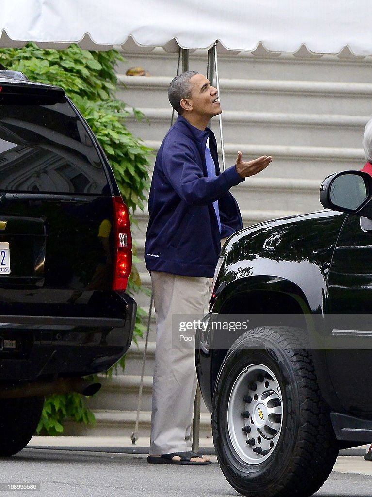 U.S. President Barack Obama checks for rain as he prepares to depart the South Portico of the White House on May 18, 2013 in Washington, DC. Obama was leaving for a round of golf with U.S. Secretary of Health and Human Services Kathleen Sebelius.