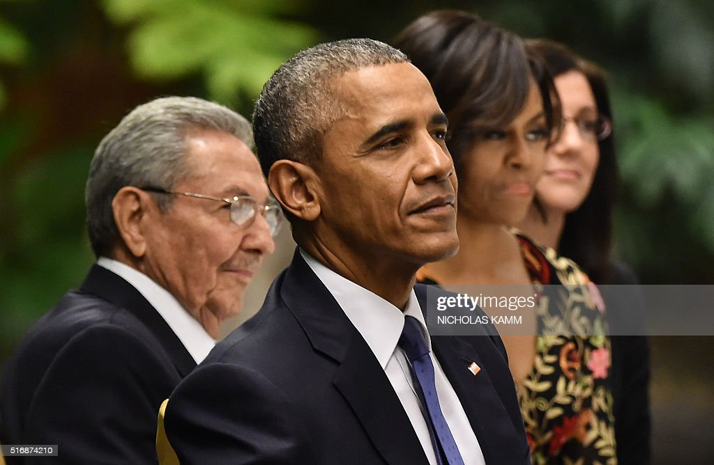 US President Barack Obama (front), Cuban President Raul Castro (L) and First Lady Michelle Obama (R) listen to music during the state dinner at the Revolution Palace in Havana on March 21, 2016. Obama and Castro vowed Monday in Havana to set aside their differences in pursuit of what the US president called a 'new day' for the long bitterly divided neighbors. AFP PHOTO/Nicholas KAMM / AFP / NICHOLAS