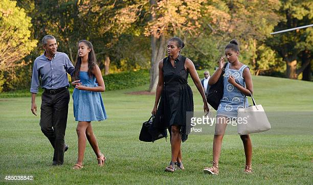 S President Barack Obama daughters Sasha and Malia and first lady Michelle Obama arrive at the White House August 23 2015 in Washington DC The first...