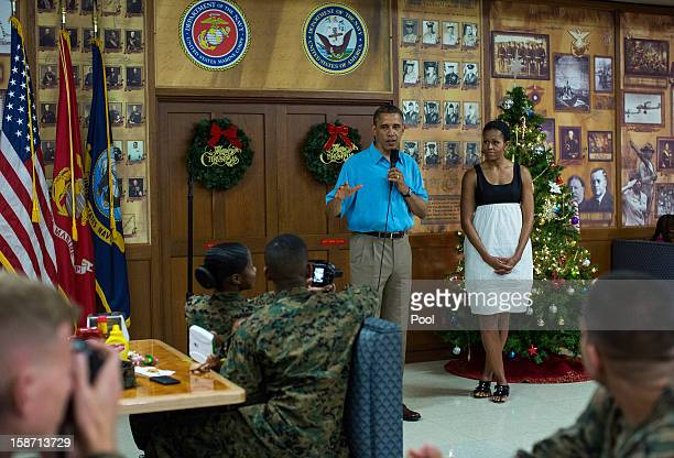 President Barack Obama delivers remarks while First Lady Michelle Obama listens as they visited military personnel eating Christmas Dinner at...