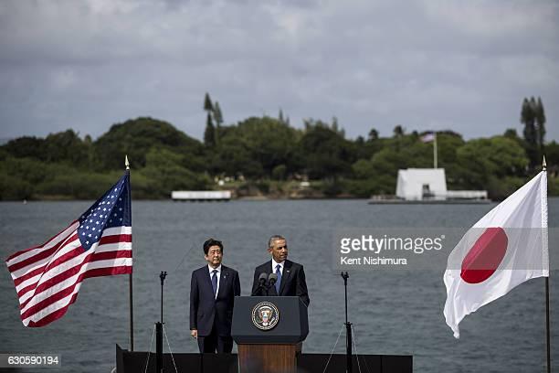 S President Barack Obama delivers remarks while Japanese Prime Minister Shinzo Abe listens at Joint Base Pearl Harbor Hickam's Kilo Pier on December...