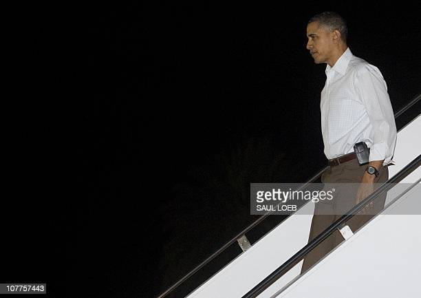US President Barack Obama disembarks after arriving on Air Force One at Hickam Air Force Base in Honolulu Hawaii late on December 22 2010 Obama...