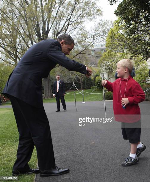President Barack Obama does a fist bump with Ethan Gibbs the son of Press Secretary Robert Gibbs after arriving by Marine One on the South Lawn of...