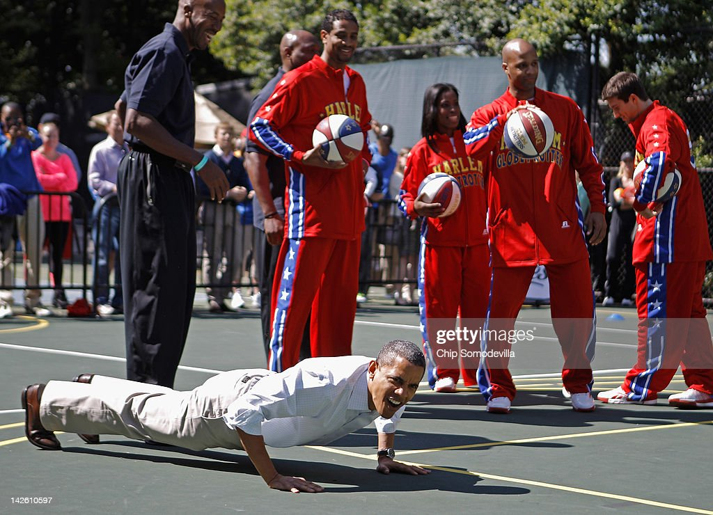U.S. President Barack Obama (R) does pushups as members of the Harlem Globetrotters look on during the annual Easter Egg Roll on the White House tennis court April 9, 2012 in Washington, DC. Thousands of people are expected to attend the 134-year-old tradition of rolling colored eggs down the White House lawn that was started by President Rutherford B. Hayes in 1878.