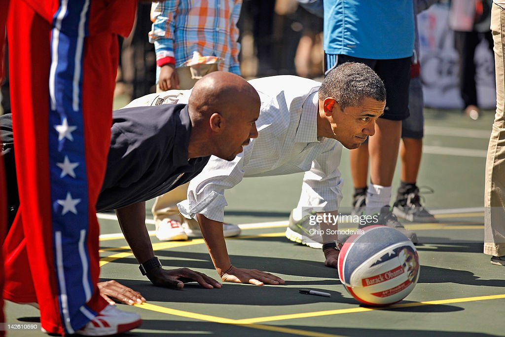 U.S. President Barack Obama (R) does pushups with retired NBA star Bruce Bowen during the annual Easter Egg Roll on the White House tennis court April 9, 2012 in Washington, DC. Thousands of people are expected to attend the 134-year-old tradition of rolling colored eggs down the White House lawn that was started by President Rutherford B. Hayes in 1878.