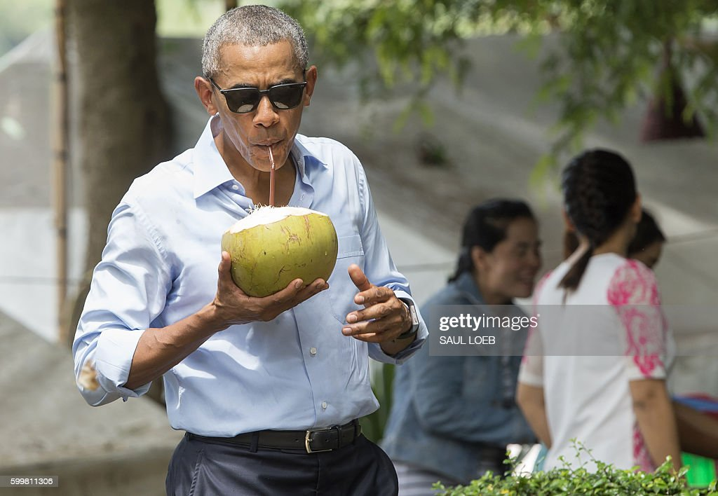 President Barack Obama drinks from a coconut as he makes a surprise stop for a drink alonside the Mekong River in Luang Prabang on September 7, 2016. Obama became the first US president to visit Laos in office, touching down in Vientiane late on September 5 for a summit of East and South East Asian leaders. / AFP / SAUL