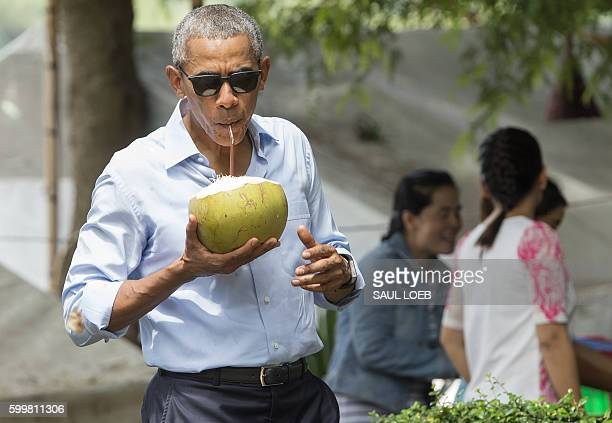 President Barack Obama drinks from a coconut as he makes a surprise stop for a drink alonside the Mekong River in Luang Prabang on September 7 2016...