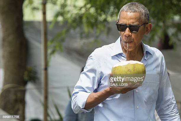 US President Barack Obama drinks from a coconut as he makes a surprise stop for a drink alonside the Mekong River in Luang Prabang on September 7...