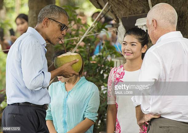 US President Barack Obama drinks from a coconut as he makes a surprise stop for a drink alongside the Mekong River in Luang Prabang on September 7...