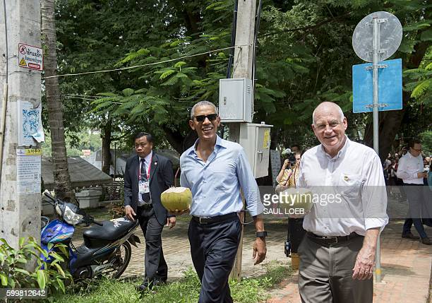 US President Barack Obama drinks from a coconut with the US Ambassador to Laos Daniel Clune as he makes a surprise stop for a drink alongside the...