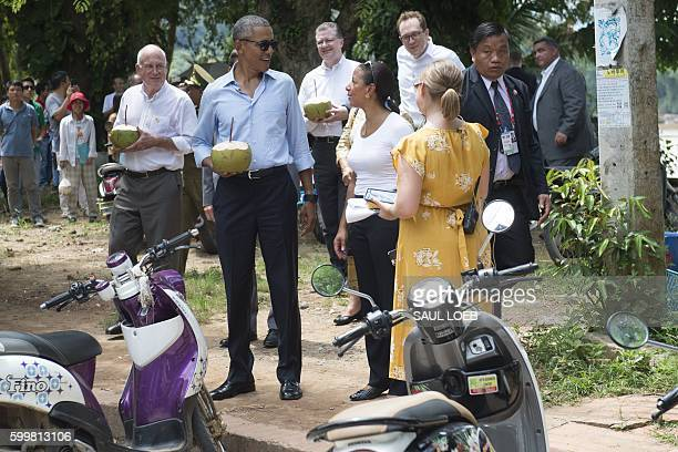 US President Barack Obama drinks from a coconut with US Ambassador to Laos Daniel Clune as he makes a surprise stop for a drink alongside the Mekong...