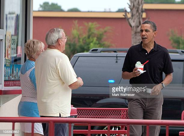 US President Barack Obama eats his mint chocolate chip ice cream as he talks to the Bruster's Real Ice Cream shop owners Joan and Larry Epperly...