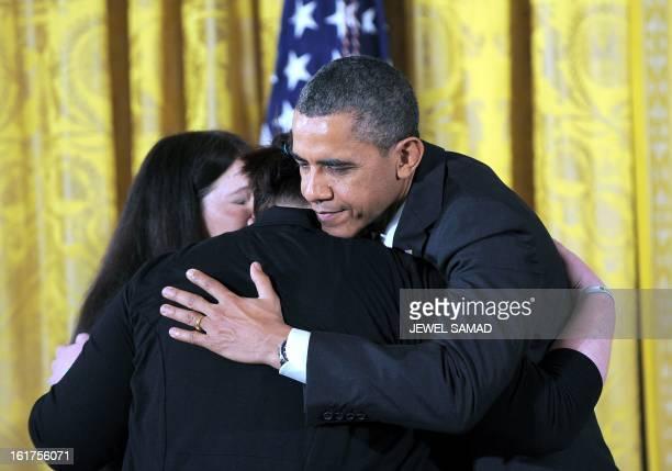 President Barack Obama embrace family members of slain Sandy Hook Elementary School teacher's aide Rachel Davino before presenting them a 2012...