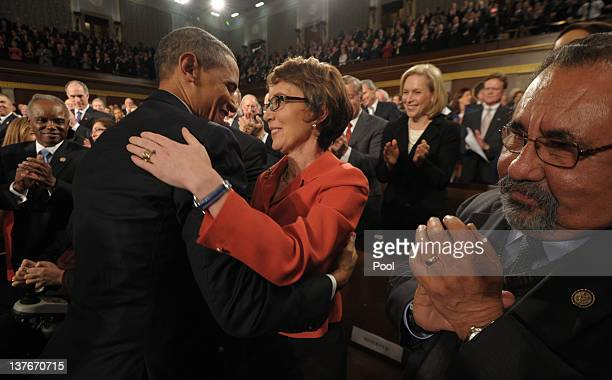 President Barack Obama embraces U.S. Rep. Gabrielle Giffords as members of Congress applaud before his State of the Union address before a joint...