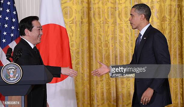 US President Barack Obama extends to shakes hands with Japan's Prime Minister Yoshihiko Noda during a joint press conference in the East Room at the...