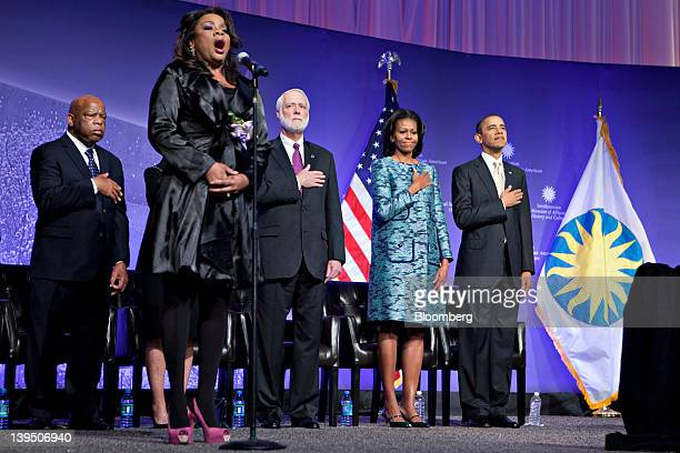 US President Barack Obama far right and first lady Michelle Obama listen to the national anthem at the groundbreaking ceremony of the Smithsonian...
