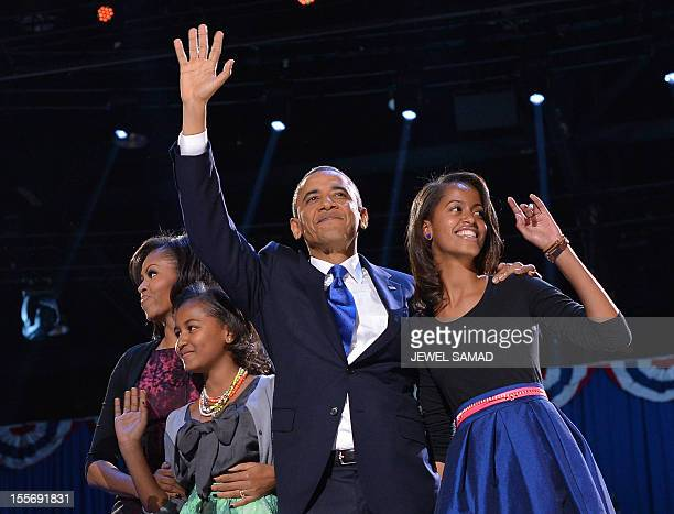 US President Barack Obama First Lady Michelle and daughters Sasha and Malia wave to supporters on election night November 6 2012 in Chicago Illinois...