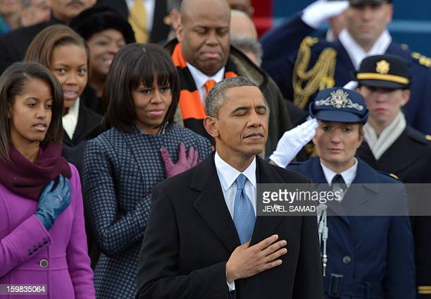 President Barack Obama First Lady Michelle Obama and daughter Malia listen to Beyonce sing the National Anthem during the 57th Presidential...