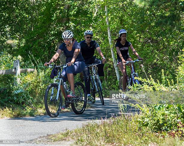 S President Barack Obama First Lady Michelle Obama and daughter Malia Obama ride bikes along the Correllus State Bike Path on August 15 2014 outside...