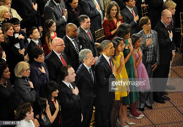 US President Barack Obama first lady Michelle Obama and daughters Malia and Sasha join the audience in the playing of the national anthem prior to...