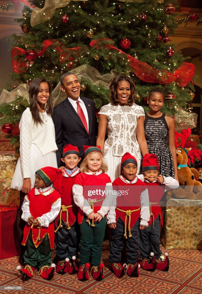 U.S. President Barack Obama, first lady Michelle Obama, and daughters Malia (left) and Sasha pose with 'elves' prior to the taping of TNT's 'Christmas in Washington' on December 15, 2013 in Washington, DC. The program benefits the Children's National Health System. Elves shown (L - R) are Elijah Jaydon Young (4), Rocco Rueda (6), Brook Rosenberg (5), and twins Dale and Delaney Crawford (4).