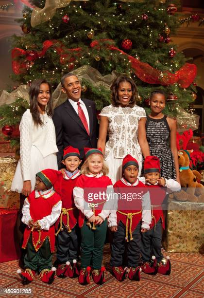 S President Barack Obama first lady Michelle Obama and daughters Malia and Sasha pose with 'elves' prior to the taping of TNT's 'Christmas in...