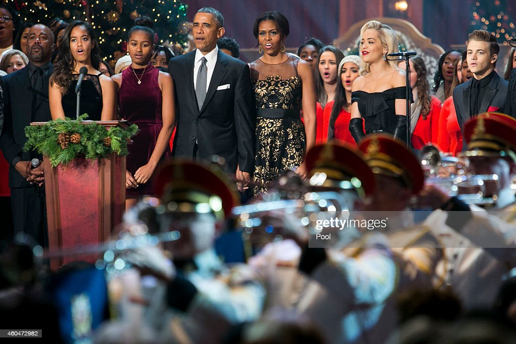U.S. President Barack Obama, first lady Michelle Obama, and daughters Malia and Sasha join the performers on stage during the taping of TNT's 'Christmas in Washington' program on December 14, 2014 in Washington, DC. They are joined on stage by (left to right) Darius Rucker, Rita Ora and Hunter Hayes. Proceeds from the concert will go to Children's National Medical Center.