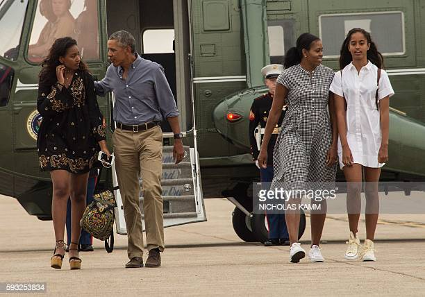 US President Barack Obama First Lady Michelle Obama and daughters Malia and Sasha walk to board Air Force One at Cape Cod Air Force Station in...