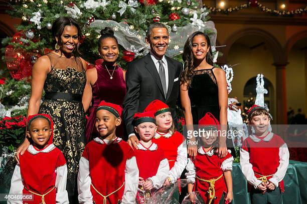 US President Barack Obama first lady Michelle Obama and daughters Sasha and Malia pose with elves prior to the taping of TNT's Christmas in...