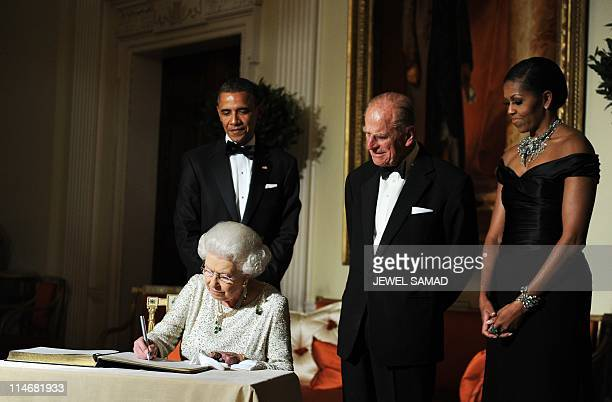 US President Barack Obama First Lady Michelle Obama and Prince Philip the Duke of Edinburgh look on as Britain's Queen Elizabeth II signs a guest...
