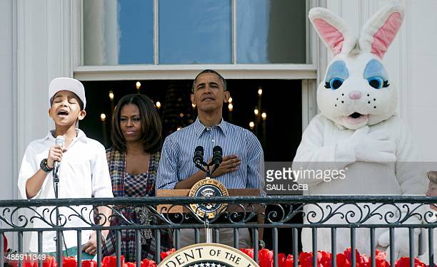 US President Barack Obama First Lady Michelle Obama and the Easter Bunny stand as 12yearold Cam Anthony sings the National Anthem during the annual...