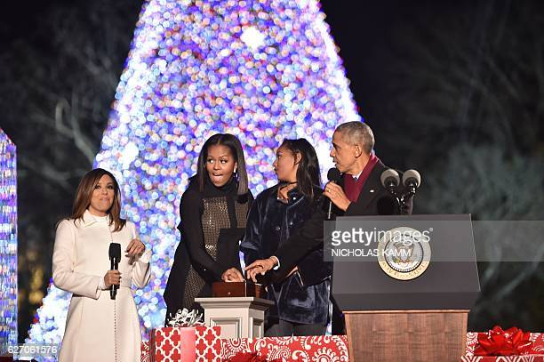 US President Barack Obama First Lady Michelle Obama and their daughter Sasha push a button to light the National Christmas Tree on the Ellipse of the...