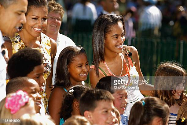 US President Barack Obama first lady Michelle Obama and their daughters Sasha and Malia pose for photographs with children after officially opening...