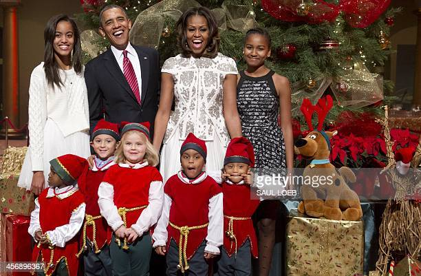 President Barack Obama, First Lady Michelle Obama and their daughters, Sasha and Malia , pose for photographs alongside children dressed as elves,...