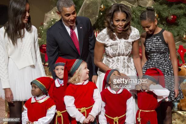 President Barack Obama, First Lady Michelle Obama and their daughters Sasha and Malia pose for photographs alongside children dressed as elves, who...