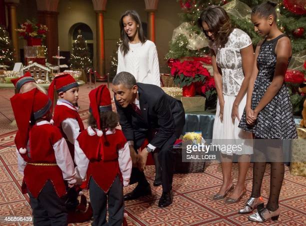 President Barack Obama, First Lady Michelle Obama and their daughters Sasha and Malia speak with children dressed as elves, who are or were patients...