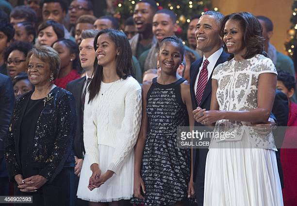 US President Barack Obama First Lady Michelle Obama and their daughters Sasha and Malia sing onstage during a taping of TNT's Christmas in Washington...