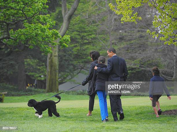US President Barack Obama First Lady Michelle Obama and their daughters Malia and Sasha walk with the new family dog Bo a Portuguese water dog on...