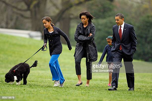 S President Barack Obama first lady Michelle Obama and their daughters Sasha and Malia introduce their new dog a Portuguese water dog named Bo to the...